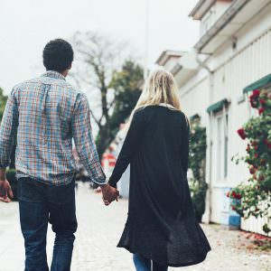 Couple walking the cobblestone streets of a small town in Scandinavia